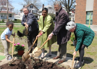 Mayor Jackson and others help to plant a tree at Louisa May Alcott elementary school.